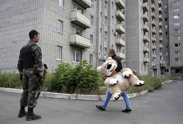 "A local resident carries a toy bear as a Ukrainian serviceman patrol on September 8, 2014 near a residential building damaged during recent shelling in the Avdeevka, 5 kilometres north of Donetsk . Ukrainian President Petro Poroshenko said on Monday that Kiev had managed to ""free"" 1,200 people taken captive by pro-Russian rebels during their five-month separatist uprising AFP PHOTO/ANATOLII STEPANOV"