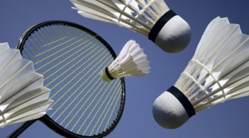 Badminton action. Badminton racket and shuttlecocks close-up and high sky blue