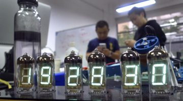 "In this Wednesday, April 20, 2016 photo, Eric Pan of Seeed, left, which is a contract manufacturer for ""makers"" – tinkerers, hackers, designers and inventors who celebrate open-source hardware – talks with a friend while a homemade digital clock is seen in the foreground in Shenzhen, China. Pan helped foster the growing maker movement in Shenzhen, which is reinventing itself from a powerhouse manufacturing ""special economic zone"" that powered China's economic ascent into the country's version of Silicon valley, shedding low-cost factory production for growth staked on finance, technology and culture. (AP Photo/Kelvin Chan)"