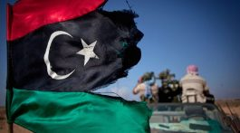 In this Wednesday, Sept. 28, 2011 photo, a pre-Gadhafi flag flies from a vehicle as revolutionary fighters patrol near the airport, in Sirte, Libya. (AP Photo/Manu Brabo)