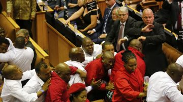 """Economic Freedom Fighters in red are forcibly removed from parliament in Cape Town, South Africa, Thursday, Feb. 9, 2017. Parliament descended into chaos with opposition lawmakers denouncing President Jacob Zuma as a """"scoundrel"""" and """"rotten to the core"""" because of corruption allegations and then brawling with guards who dragged them out of the chamber. (AP Photo/Sumaya Hisham, Pool)"""