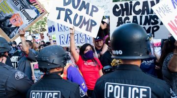Police form a line to contain protesters outside a campaign rally for Republican presidential candidate Donald Trump on Thursday, June 2, 2016, in San Jose, Calif.  A group of protesters attacked  Trump supporters who were leaving the presidential candidate's rally in San Jose on Thursday night. A dozen or more people were punched, at least one person was pelted with an egg and Trump hats grabbed from supporters were set on fire on the ground. (AP Photo/Noah Berger)