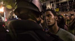A protester stares at riot police during a demonstration against police brutality in Charlotte, North Carolina, on September 21, 2016, following the shooting of Keith Lamont Scott the previous day. A protester in Charlotte, North Carolina was fatally shot by a civilian during a second night of unrest after the police killed a black man, officials said. / AFP PHOTO / NICHOLAS KAMMNICHOLAS KAMM/AFP/Getty Images ** OUTS - ELSENT, FPG, CM - OUTS * NM, PH, VA if sourced by CT, LA or MoD **