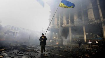 """An anti-government protester holds a Ukranian flag as he advances through burning barricades in Kiev's Independence Square February 20, 2014. Ukrainian protesters hurling petrol bombs and paving stones drove riot police from the central square in Kiev on Thursday despite a """"truce"""" which embattled Ukrainian President Viktor Yanukovich said he had agreed with opposition leaders.  REUTERS/Yannis Behrakis (UKRAINE - Tags: CIVIL UNREST POLITICS)"""