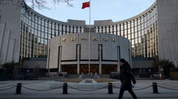 A pedestrian walks past the People's Bank of China (PBOC) headquarters in Beijing, China, on Friday, March 1, 2013. China's economy expanded 7.9 percent in the final three months of 2012 from a year earlier, the first pickup in two years. The pace may accelerate to 8.2 percent in the three months through March, according to the median estimate of 23 analysts surveyed by Bloomberg News in February. Photographer: Tomohiro Ohsumi/Bloomberg
