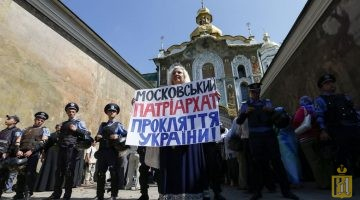 "A protester holds a placard as Interior Ministry members stand guard near the Kiev Pechersk Lavra monastery on the day of the election of the Primate of the Ukrainian Orthodox Church of the Moscow Patriarchate, in Kiev August 13, 2014. Former Primate of the Ukrainian Orthodox Church of the Moscow Patriarchate, Metropolitan Vladimir of Kiev and All Ukraine died on July 5. An inscription on the placard reads, ""The Moscow Patriarchate - a curse for Ukraine"".  REUTERS/Gleb Garanich (UKRAINE - Tags: RELIGION CIVIL UNREST)"
